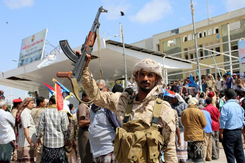 A southern Yemeni separatist fighter waves his rifle at the site of an anti-government protest in the port city of Aden