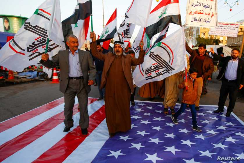 Iraqi people walk on a U.S. flag in a protest after an airstrike at the headquarters of Kataib Hezbollah militia group in Qaim, in the holy city of Najaf